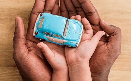 father and son holding blue toy car