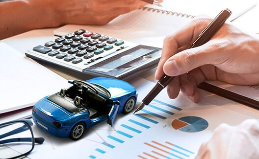 man pointing on graphs with blue car and calculator background