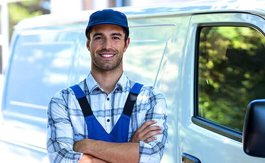 man crossed arms with white van background