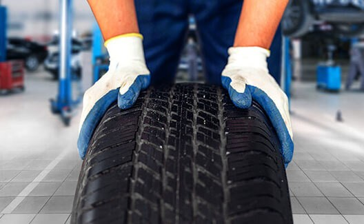 man with gloves holding a tyre
