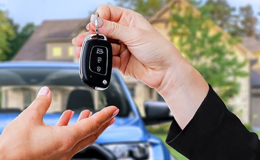 car dealer handing keys to owner