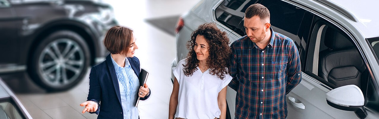 couple talking to a woman car dealer