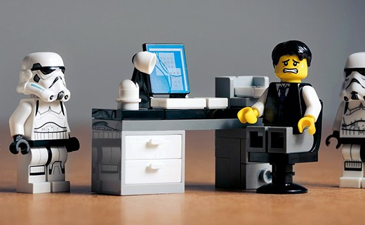 lego man at desk with stormtroopers