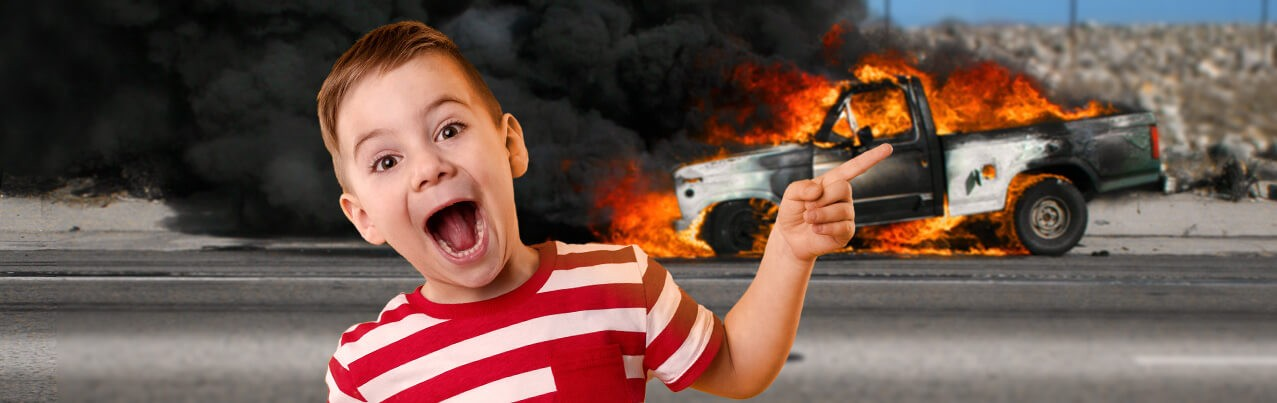 Smiling boy pointing at burning vehicle