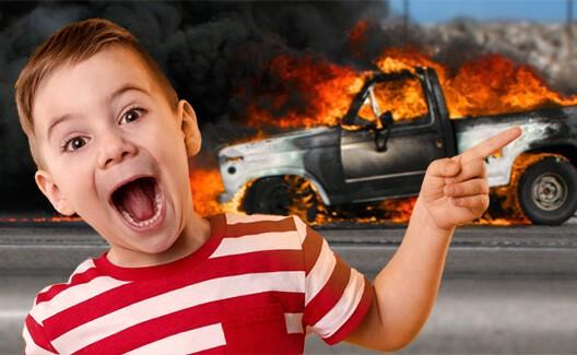 Smiling boy pointing at burning vehicle